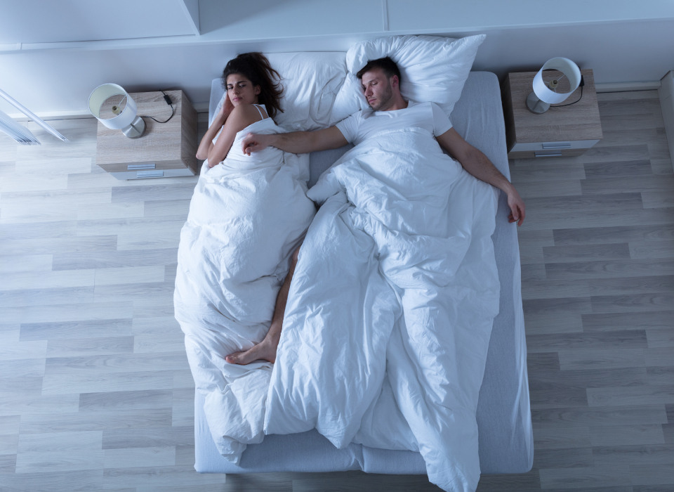 man and woman sleeping in bed - He's on his back taking up most of the bed.