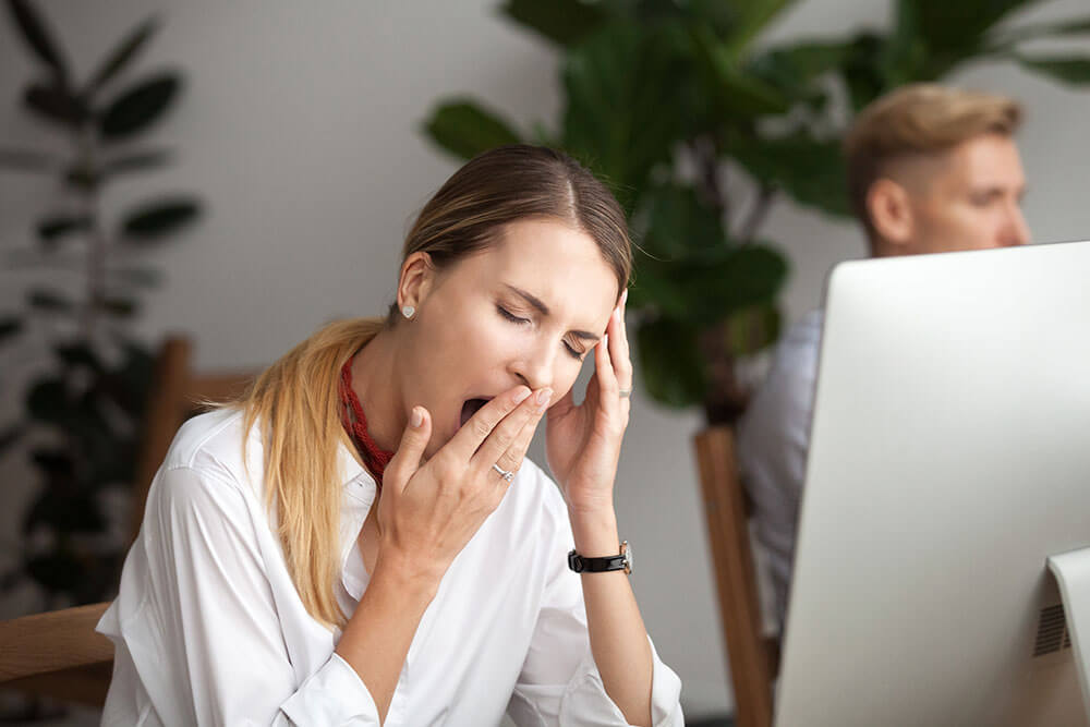 Woman sitting in front of a computer, yawning and holding her hand up to her mouth