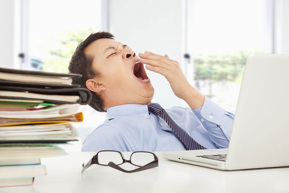 Man yawning in front of a desk with a laptop with a pile of work and glasses