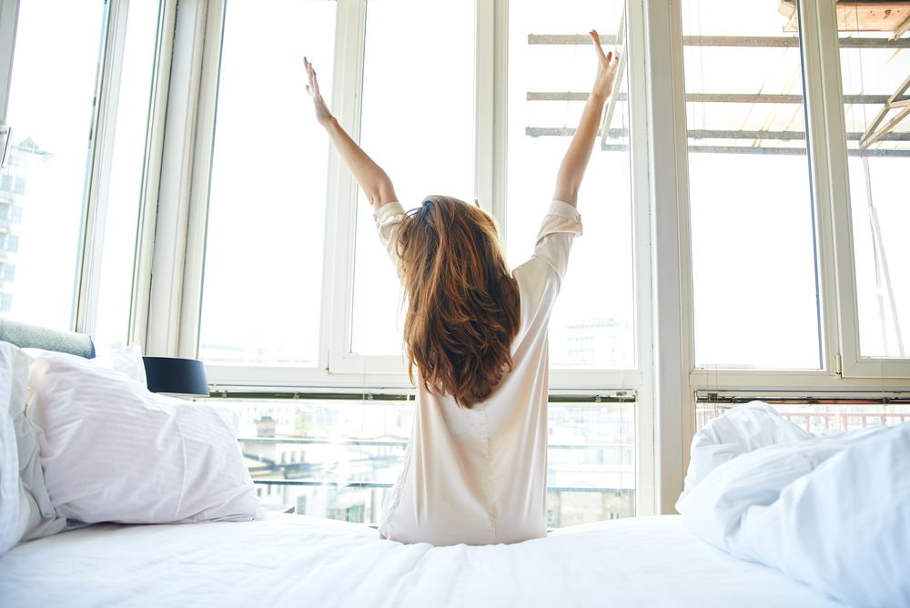 woman with long brown hair stretching in a bright room after waking up