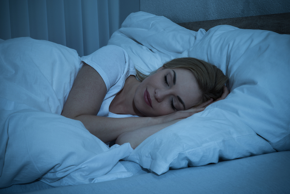 Woman sleeping peacefully in a white bed