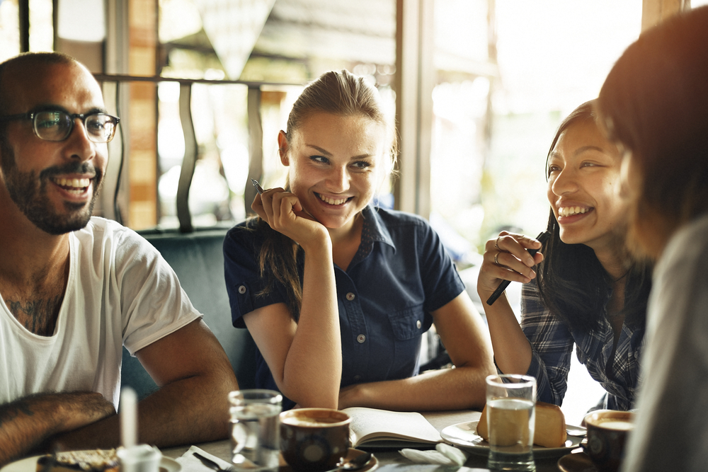 group of young diverse people sitting in a coffee shop talking and smiling