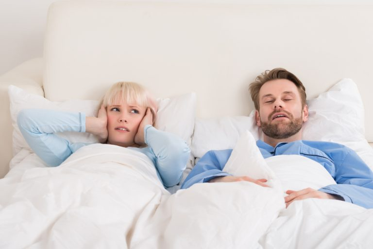 Couple laying in a white bed as the man sleeps and the woman covers her ears