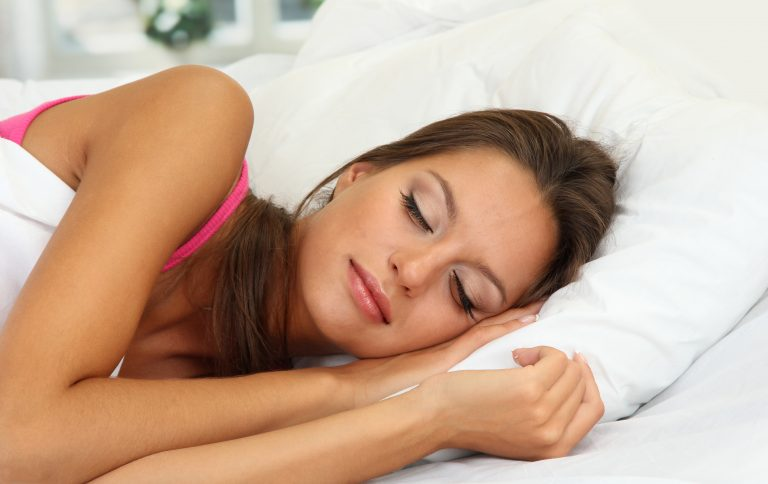 woman with dark hair laying in a white bed sleeping